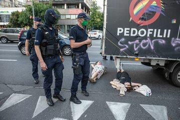 Osoby leżące pod furgonetką z hasłami anty-LGBT