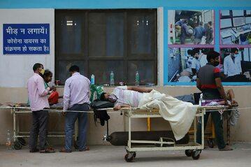 Pacjenci oczekują na wolne łóżka przed szpitalem w New Delhi