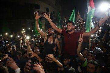 Palestyńczycy świętują zawieszenie broni między Izraelem a Hamasem w Strefie Gazy, widoczne flagi Hamasu i Autonomii Palestyńskiej