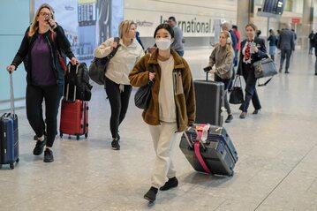 Podróżna w masce medycznej na lotnisku Heathrow