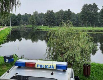 Policyjny radiowóz nad stawem, z którego wyłowiono ciało 21-latki