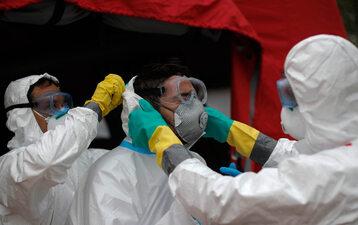 Pracownicy służby zdrowia ubierają się w kombinezony ochronne