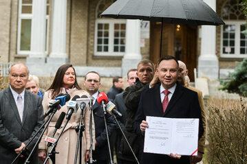 Prezydent Andrzej Duda pokazuje podpisaną specustawę, która ma pomóc w walce z koronawirusem