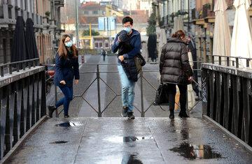 Przechodnie w maskach na ulicy Mediolanu, zdjęcie ilustracyjne