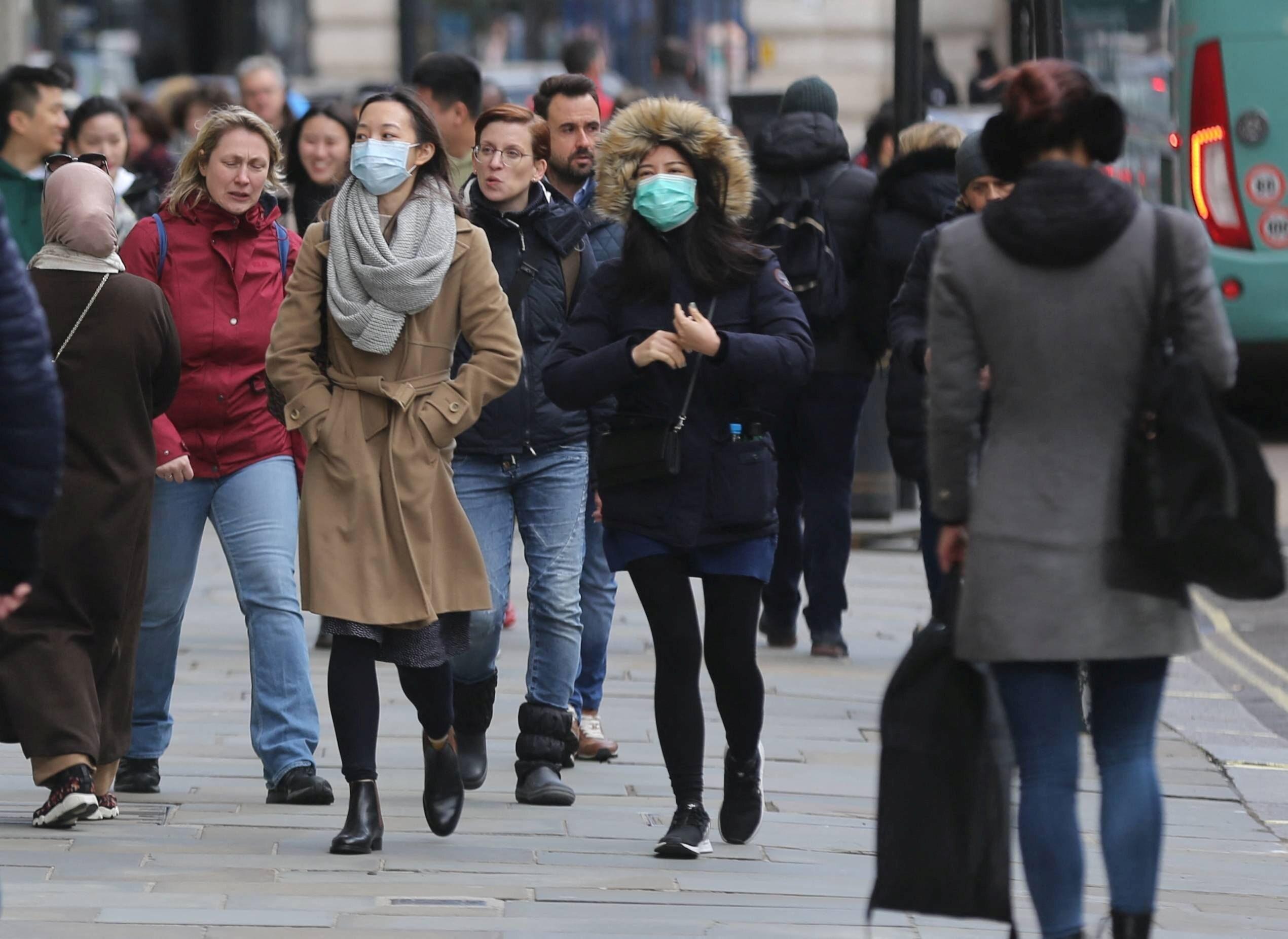 Przechodnie w maskach ochronnych na ulicach Londynu