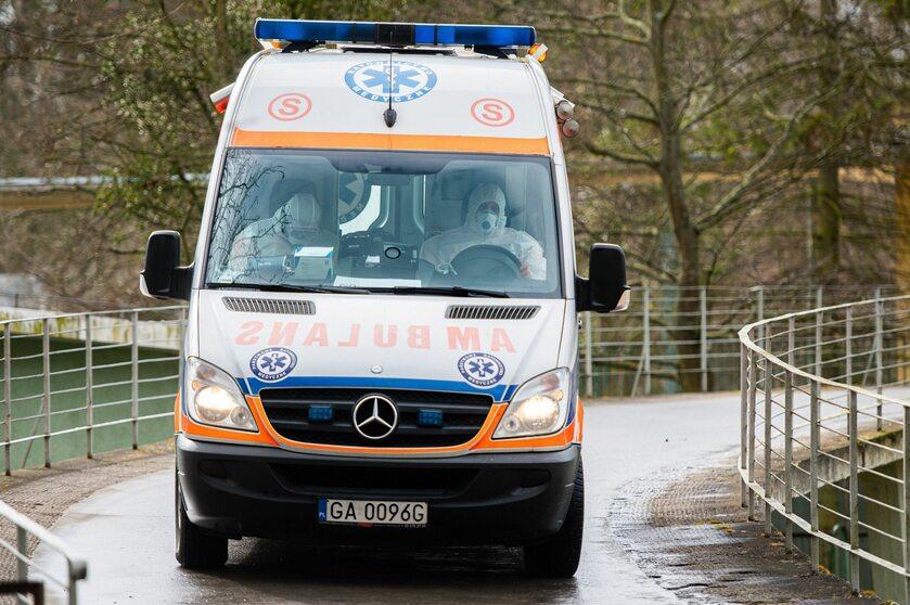 Ratownicy medyczni w kombinezonach wyjeżdżają z Pomorskiego Centrum Chorób Zakaźnych i Gruźlicy