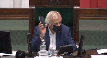 Ryszard Terlecki pokazuje znaleziony telefon w Sejmie