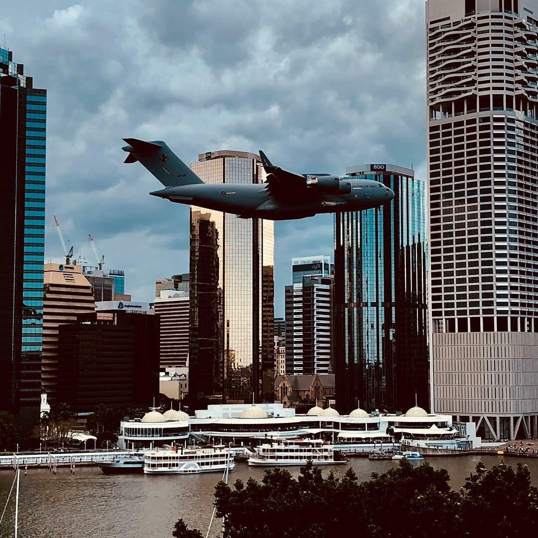 Samolot transportowy C-130 Hercules uchwycony między wieżowcami Brisbane