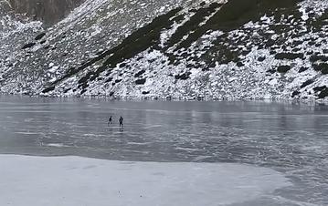 Turyści jeżdżący na łyżwach po Czarnym Stawie Gąsienicowym