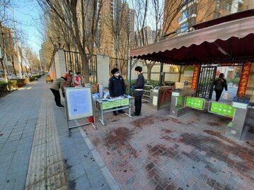 Wolontariusze sprawdzający temperaturę mieszkańców osiedla w Pekinie