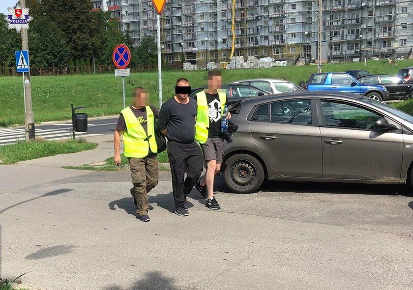 Zatrzymany mężczyzna w towarzystwie policjantów