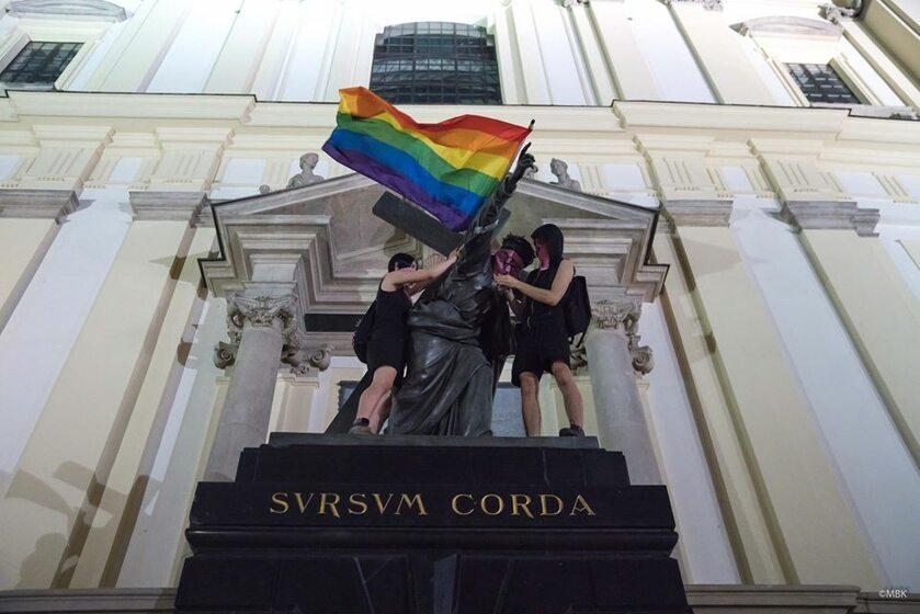 Zawieszenie tęczowej flagi na pomniku Chrystusa przed Bazyliką św. Krzyża na Krakowskim Przedmieściu
