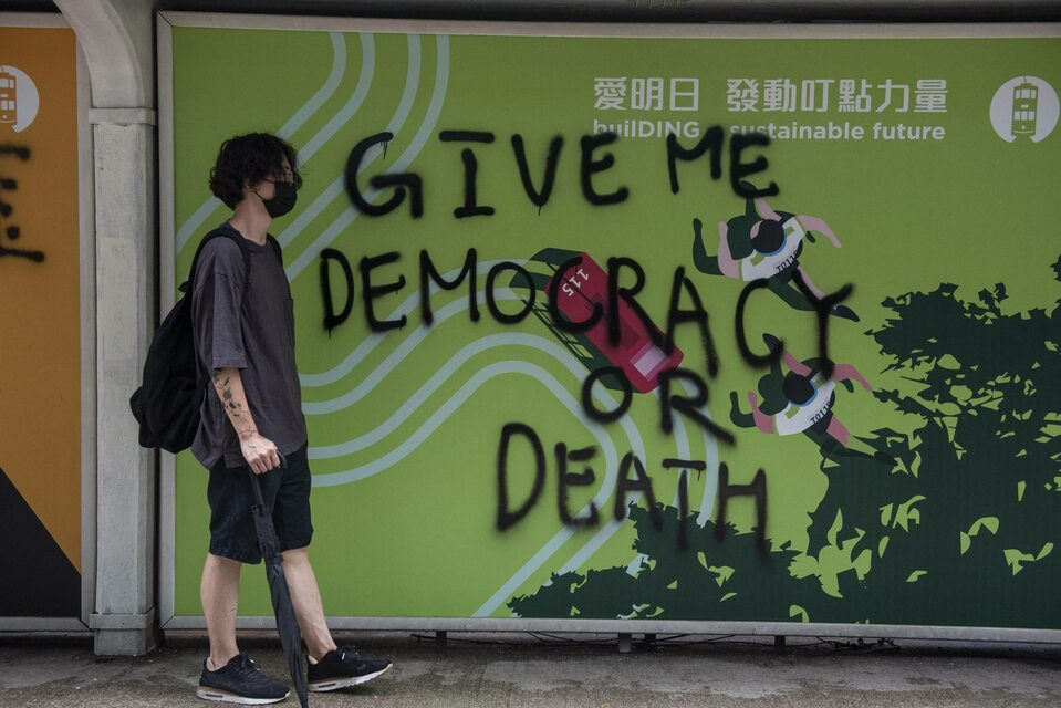 """Zdjęcie z protestów w Hongkongu. Na ścianie hasło: """"Dajcie mi demokrację, albo śmierć"""""""
