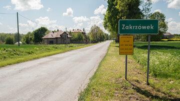 Znak drogowy informujący o wjeździe do Zakrzówka z tabliczką doczepioną przez Barta Staszewskiego