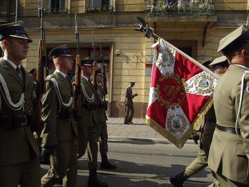 """Żołnierze ze sztandarem. Na nim hasło """"Bóg, Honor, Ojczyzna"""""""